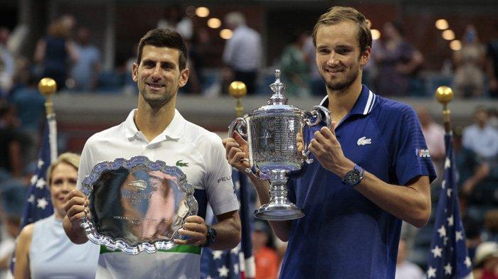 Petenis Rusia Rusia Daniil Medvedev (kanan) dan petenis Serbia Novak Djokovic memegang piala mereka setelah laga final US Open di USTA Billie Jean King National Tennis Center  New York, Minggu 12 September 2021.