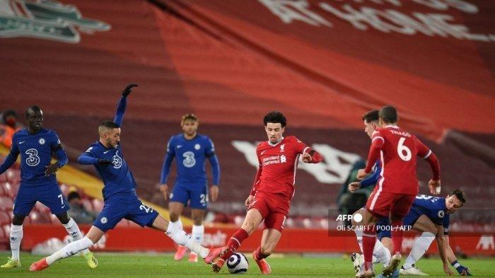Gelandang Liverpool Inggris Curtis Jones (tengah) mengalahkan tantangan dari gelandang Maroko Chelsea Hakim Ziyech (kiri) selama pertandingan sepak bola Liga Utama Inggris antara Liverpool dan Chelsea di Anfield di Liverpool, barat laut Inggris pada 4 Maret 2021.
