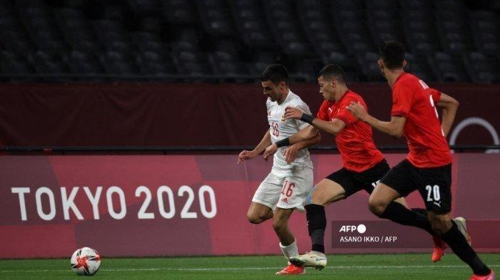 Gelandang Spanyol Pedri Gonzalez (kiri) berlari dengan bola melewati pemain Mesir selama pertandingan sepak bola putaran pertama grup C putra Olimpiade Tokyo 2020 antara Mesir dan Spanyol di Sapporo Dome di Sapporo pada 22 Juli 2021.