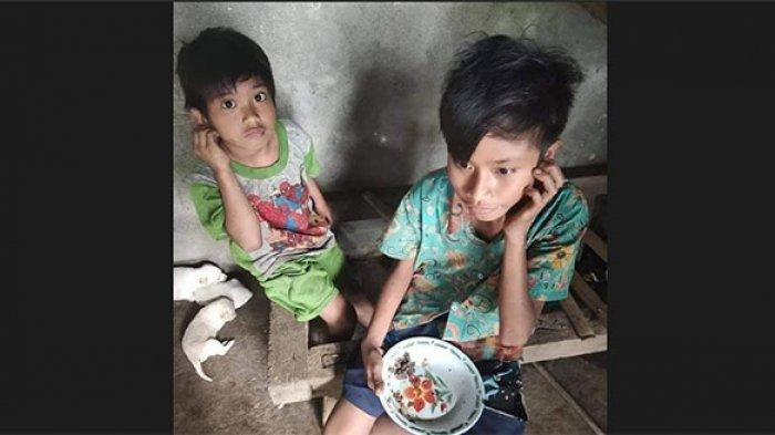 Ketut Pait bersama adiknya saat makan disekitar rumahnya. Bocah yatim piatu ini hidup serba kekurangan.
