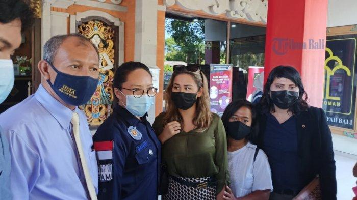 Tribun Bali/Zaenal Nur Arifin Leia Se (kemeja hijau) didampingi petugas imigrasi saat akan memasuki mobil untuk menuju Bandara Internasional I Gusti Ngurah Rai Bali - Viral Bule Lukis Wajah Menyerupai Masker di Bali Akhirnya Jalani Deportasi