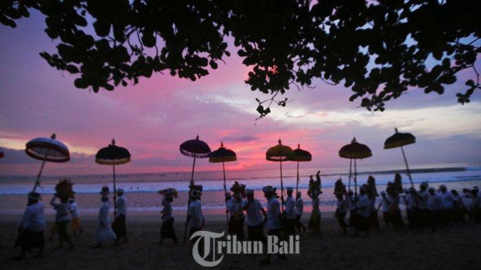 Iringan pemedek krama Desa adat kuta saat menggelar Upacara melasti di pantai Kuta, Senin (4/3/2019) dengan latar warna matahari tenggelam.