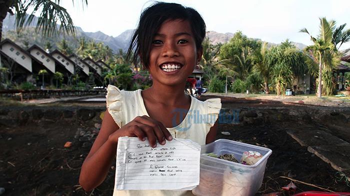 Ni Luh Lisa menunjuk pesan berbahasa Inggris saat berjualan garam souvenir kepada  turis asing di kawasan Pantai Amed-Bali, Senin (21/9/2015).