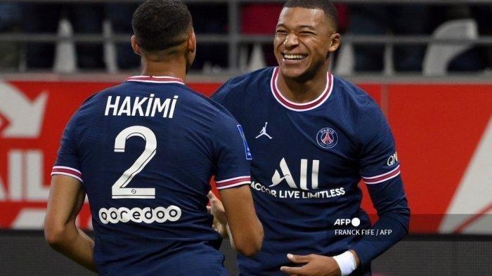 Pemain depan Prancis Paris Saint-Germain Kylian Mbappe (kanan) merayakan mencetak gol kedua timnya dengan rekan setimnya bek Maroko Achraf Hakimi selama pertandingan sepak bola L1 Prancis antara Stade de Reims dan Paris Saint-Germain (PSG) di Stade Auguste Delaune di Reims, Prancis utara pada 29 Agustus 2021. FRANCK FIFE / AFP