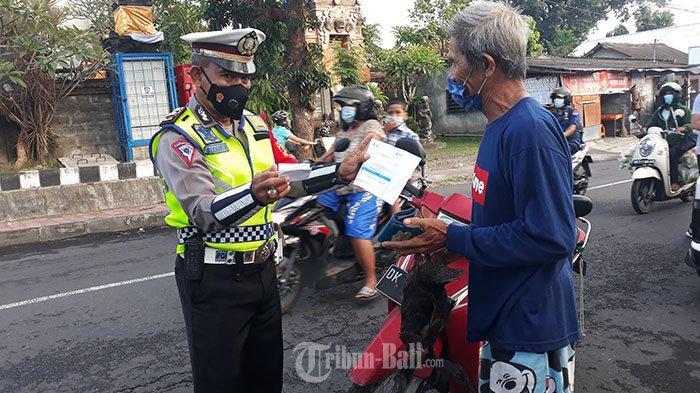 Petugas kepolisian melaksanakan penyekatan terkait PPKM Darurat di Jalan Trengguli Penatih Denpasar, Minggu 11 Juli 2021.