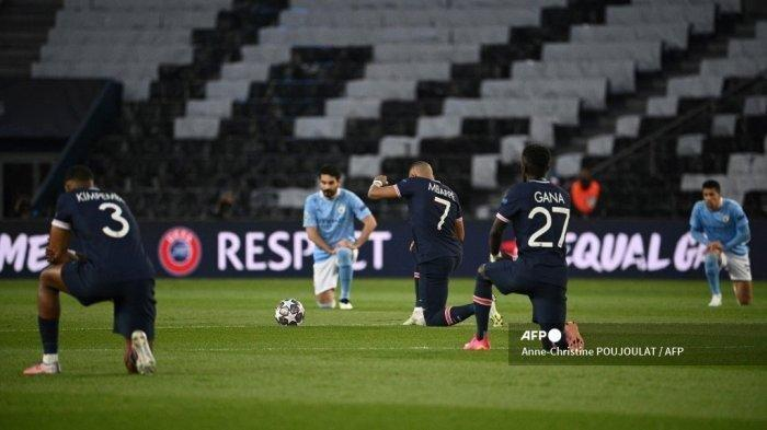 Penyerang Prancis Paris Saint-Germain Kylian Mbappe (tengah) berlutut di lapangan melawan rasisme sebelum pertandingan sepak bola semifinal leg pertama Liga Champions UEFA antara Paris Saint-Germain (PSG) dan Manchester City di stadion Parc des Princes di Paris pada 28 April 2021.