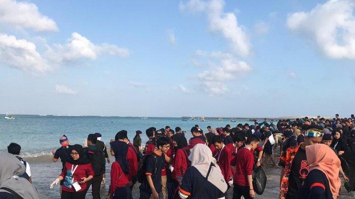 Unud Ajak Peserta dan Delegasi PIMNAS Bersihkan Sampah Plastik dan Lepas Tukik di Pantai Kelan