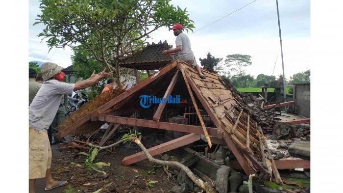 Warga sedang membersihksn puing bangunan di Pura Subak Bedugul Desa Takmung,yang  roboh dan rata dengan tanah akibat diterjang angin kencang, Selasa malam (23/2).