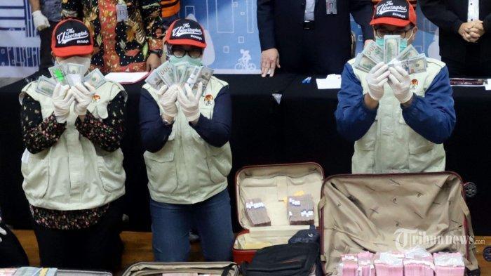 Penyidik KPK menunjukkan barang bukti uang hasil suap saat konferensi pers terkait operasi tangkap tangan (OTT) KPK dalam kasus dugaan suap bantuan sosial (bansos) Covid-19 di Kantor KPK, Jakarta Selatan, Minggu (6/12/2020) dini hari. KPK menetapkan lima tersangka termasuk Menteri Sosial, Juliari P Batubara terkait dugaan suap bantuan sosial Covid-19 dan mengamankan total uang sejumlah Rp 14,5 miliar yang terdiri dari mata uang rupiah dan mata uang asing. Rinciannya yakni Rp 11,9 miliar, USD 171.085, dan sekitar SGD 23.000.