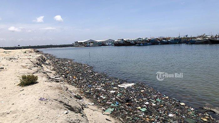 Tumpukan pasir hasil reklamasi di kawasan Pelabuhan Benoa, Denpasar, Bali, tampak kumuh, Sabtu (19/9/2020). Terlihat sampah plastik, botol, dan kaleng berserakan di sepanjang pesisir teluk tepatnya di dekat kapal-kapal ikan bersandar di Palabuhan Benoa.