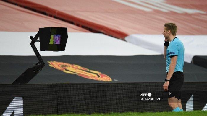 Wasit Lawrence Visser menyaksikan insiden pada monitor tayangan ulang setelah tinjauan VAR sebelum mengesampingkan gol bek Inggris kelahiran Kongo kelahiran Kongo Axel Tuanzebe selama Putaran 32 Liga Europa UEFA, pertandingan sepak bola leg kedua antara Manchester United dan Real Sociedad di Old Trafford di Manchester , Inggris barat laut, pada tanggal 25 Februari 2021.