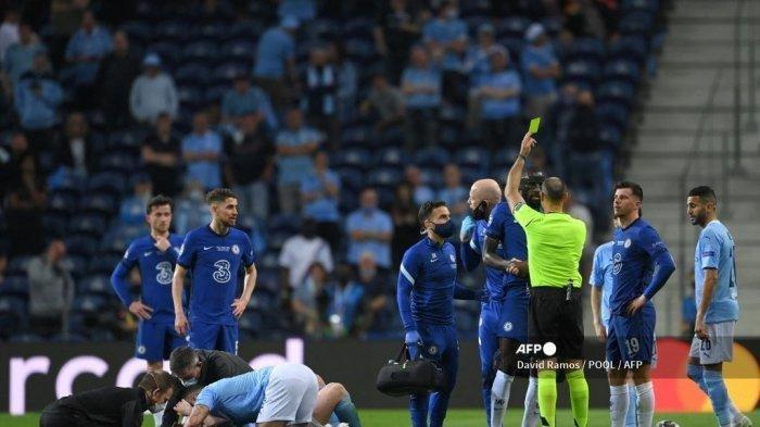 Wasit Spanyol Antonio Mateu Lahoz (Kanan ke-3) memberikan kartu kuning kepada bek Chelsea asal Jerman Antonio Ruediger (Kanan-4) saat gelandang Manchester City dari Belgia Kevin De Bruyne (kiri) menerima bantuan medis selama pertandingan sepak bola final Liga Champions UEFA antara Manchester City dan Chelsea FC di stadion Dragao di Porto pada 29 Mei 2021.
