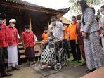 bupati-gianyar-made-mahayastra-saat-menyerahkan-bantuan-kursi-roda-pada-warga.jpg