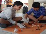 dua-orang-siswa-tengah-merekontruksi-gerabah.jpg