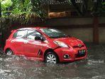 mobil-berwarna-merah-terperosok-ke-selokan-karena-banjir-menggenangi-jalan-pulau-bali.jpg