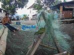 nelayan-di-pesisir-pantai-segara-sedang-memperbaiki-jajaring-ikannya.jpg