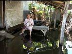 nenek-aminah-sedang-duduk-dan-pekarangan-rumahnya-masih-terendam-banjir.jpg