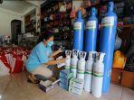 pengusaha-tas-ana-liana-dibantu-kolega-bersiap-mengirim-tabung-oksigen-di-tempat-usahanya.jpg
