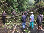 personel-polsek-tembuku-saat-melakukan-evakuasi-material-pohon-tumbang-selasa-510.jpg