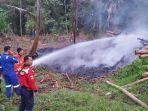 petugas-kebakaran-memadamkan-api-yang-membakar-tumpukan-kayu-jati-milik-seorang-warga.jpg