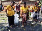 relawan-trash-hero-terlihat-memungut-sampah-plastik-saat-berlangsung-tradisi-mekotek.jpg