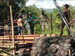 sejumlah-warga-dibantu-personel-tni-dan-polri-saat-membangun-jembatan-dimjj.jpg