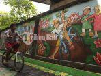 seorang-anak-melintas-disamping-mural-bertemakan-keberagaman-dan-toleransi-di-kampung-bugis.jpg
