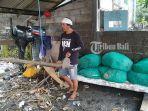 seorang-nelayan-di-pantai-segara-kusamba-sedang-membersihkan-mesin-perahunya.jpg