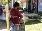 seorang-warga-sedang-mencuci-tangan-di-tempat-yang-disediakan-kantor-samsat-denpasar.jpg