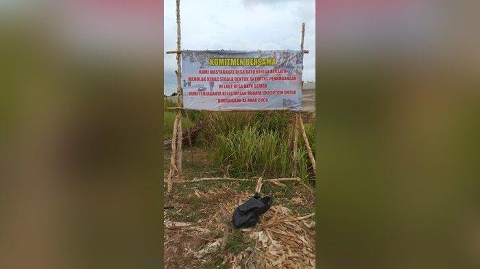 Baleho penolakan aktivitas tambang yang dipasangkan di laut Desa Batu Beriga