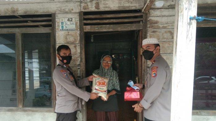 Kapolsek Lubukbesar, Ipda Hafiz Febrandani bersama Personil Polsek Lubukbesar saat membagikan Paket sembako ke warga, Jumat (16/4/2021)