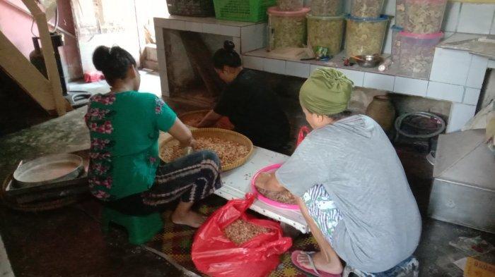 Beberapa karyawan di rumah Ellia tampak sibuk memisahkan kulit kacang untuk pembuatan kue lebaran, Kamis (22/4/2021)