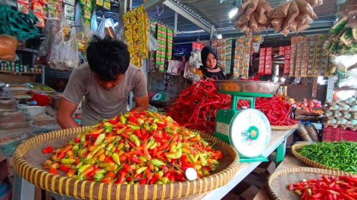 Eko (32) pedagang cabai dan bawang di Pasar Induk Kota Pangkalpinang mengenakan baju kaos bewarna coklat saat melayani pembeli Senin (19/7/2021).