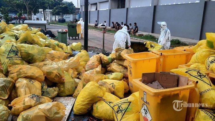 Petugas merapikan tumpukan kantong sampah plastik kuning yang menumpuk di Rumah Sakit Darurat Covid-19 Wisma Atlet, Kemayoran, Jakarta Pusat, Selasa (6/7/2021). Sejumlah petugas berpakaian alat pelindung diri (APD) lengkap tiap hari mengumpulkan kantong plastik berwarna kuning yang menumpuk berisikan APD bekas pakai, kardus makanan, dan sejumlah barang pasien yang sudah tidak terpakai. Kemudian tumpukan limbah itu disimpan di ruang khusus Tower 7 RS Darurat Covid-19 Wisma Atlet. Sekali angkut, RSD Wisma Atlet bisa mengangkut 2 ton limbah medis corona. Dalam sehari petugas dapat mengangkut 3 kali yaitu pagi, siang, dan malam hari. Tribunnews/Jeprima