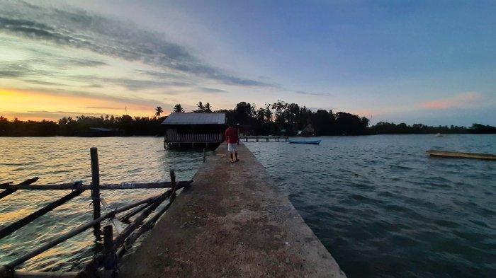 Pengunjung Pantai Bakit sedang berjalan di Dermaga dan menikmati pemandangan dan matahari terbenam atau sunset di ujung dermaga, Sabtu (4/9/2021).