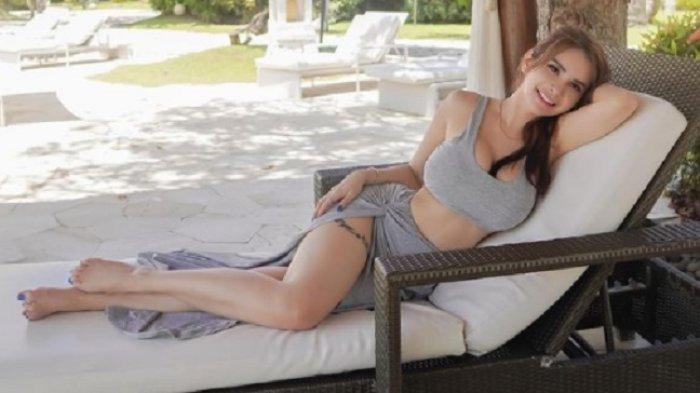 Pose Maria Vania di kursi panjang memperlihatkan tato di pahanya