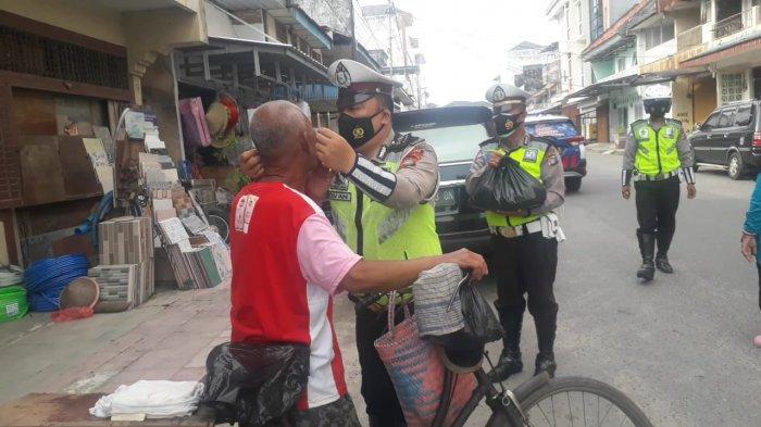 Anggota Satlantas Polres Bangka masker kepada masyarakat kurang mampu terdampak pendemi covid 19 Sabtu (17/07/2021).