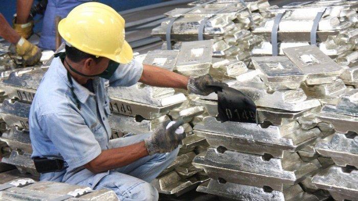 Karyawan PT Timah Tbk memeriksa timah batangan hasil produksi perusahaan.