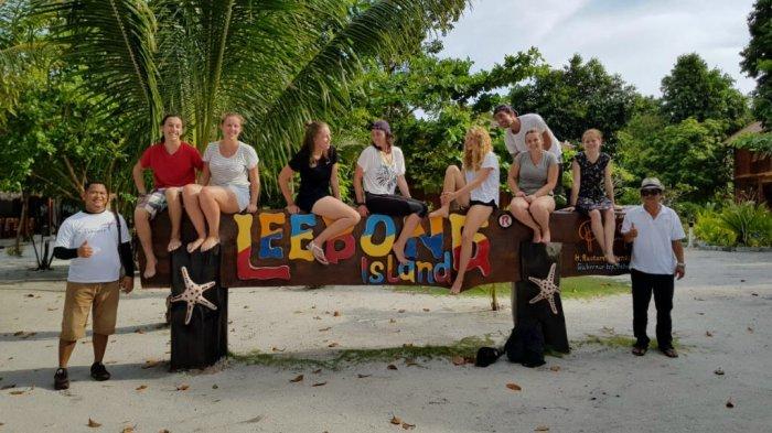 Rombongan wisatawan asing berfoto di papan nama Pulau Leebong.