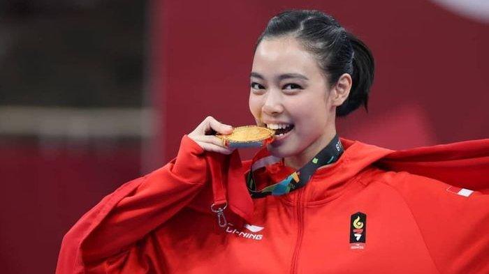 Lidswell Kwok menggigiti medali emasnya