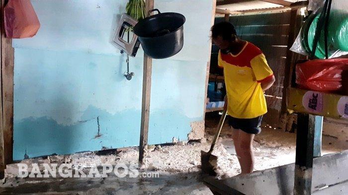 Usul (42) saat membersihkan pasir pantai yang  masuk rumah warga sekitaran pantai Pasir Padi Pangkalpinang