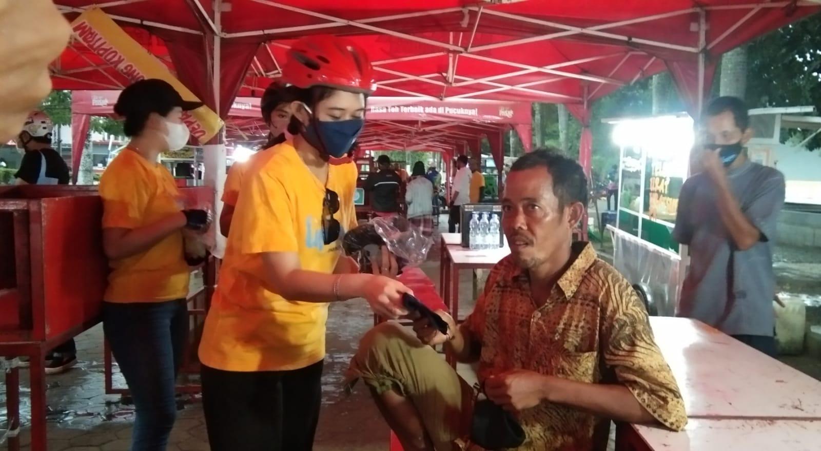 Karyawan Bank Mandiri saat membagikan masker kepada masyarakat di Alun alun Taman Merdeka (ATM), Pangkalpinang, Senin (4/10).