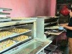 20210422-seorang-karyawan-di-rumah-ellia-sedang-memeriksa-kue-di-dalam-oven.jpg