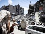 23052021-seorang-wanita-makan-es-krim-di-depan-gedung-al-shuruq-gaza.jpg
