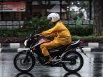 pengendara-sepeda-motor-mengenakan-jas-hujan-saat-terjadi-hujan-di-jalan-katedral.jpg