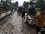 sejumlah-warga-mencoba-melintasi-banjir-yang-masih-mengenangi-jalan-daan-mogot.jpg