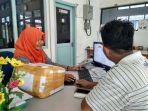 seorang-pelanggan-saat-melakukan-pengambilan-barang-di-pt-pos-indonesia-tanjungpandan_20180604_175251.jpg