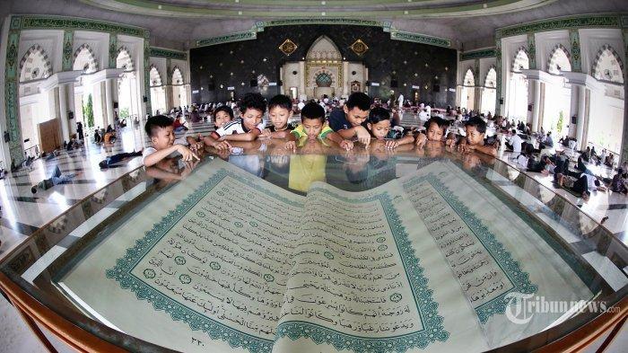 Pengunjung menyaksikan kitab suci Alquran raksasa yang dipamerkan di Masjid Raya Makassar, Jumat (11/7).