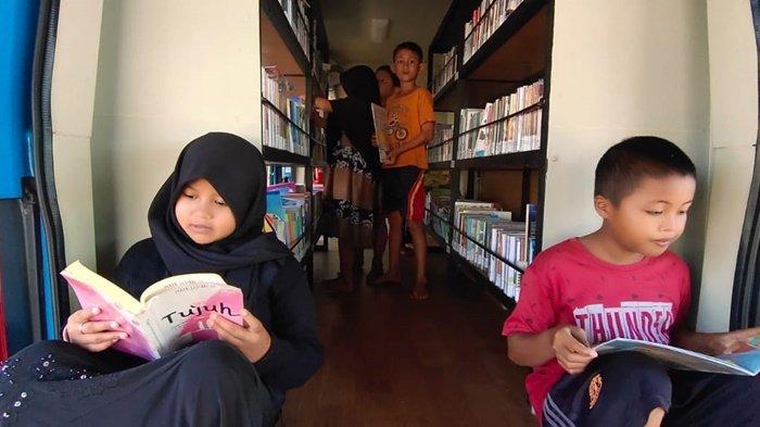 Anak-anak membaca buku di dalam Mobil Perpustakaan Keliling di lokasi TMMD ke-111 Kodim 1009/Tanahlaut di wilayah Kabupaten Tanahlaut (Tala), Provinsi Kalimantan Selatan.