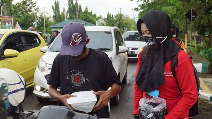 Pegawai Inspektorat HSS membagikan takjil makanan untuk berbuka puasa kepada warga yang melintas di jalan A Yani Kandangan